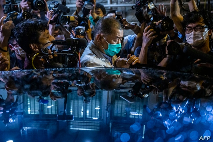 Hong Kong pro-democracy media mogul Jimmy Lai (C) pushes through a media pack to get to a waiting vehicle after being released...