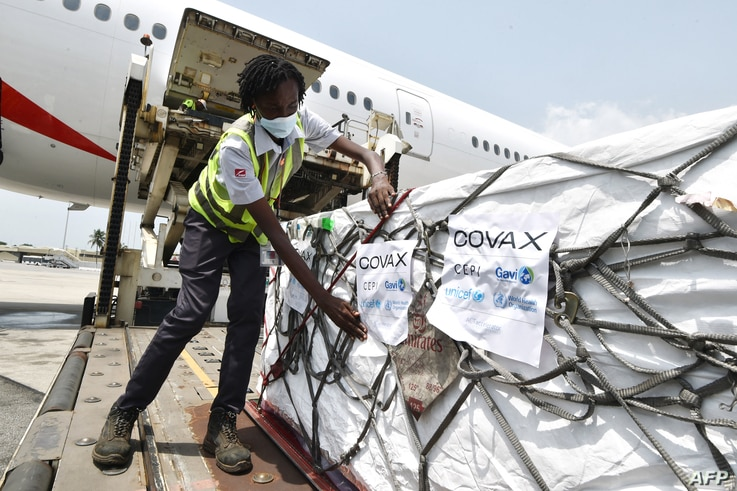 A woman puts Covax stickers as workers unload a shipment of AstraZeneca Covid-19 vaccine from a plane at Felix Houphouet Boigny...