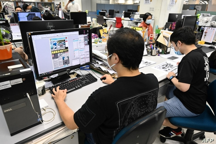 This photo taken on May 11, 2021 shows journalists working in the newsroom of the Apple Daily newspaper in Hong Kong. - A...