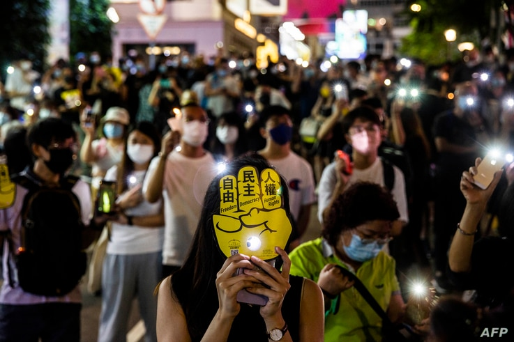 People hold up their phones with the light on in the Causeway Bay district of Hong Kong on June 4, 2021, after police closed…