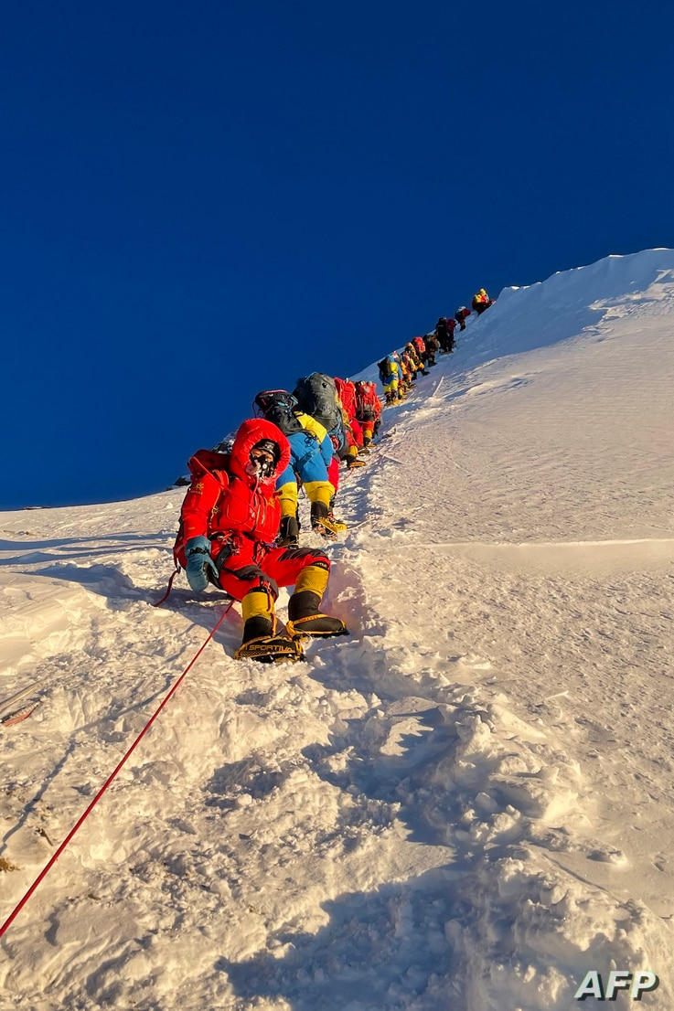 This photograph taken on May 12, 2021 shows mountaineers climbing during their ascend to summit Mount Everest (8,848.86-metre),…