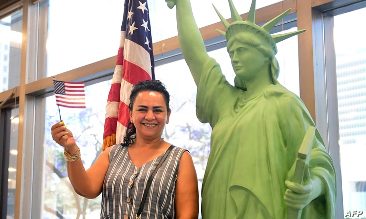 New US citizen Doris Nazarian waves the flag while posing beside a replica of the Statue of Liberty during a naturalization…