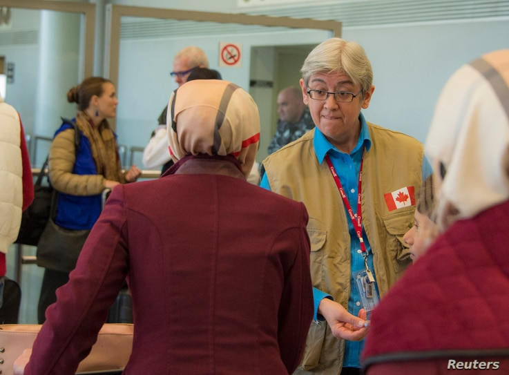Sharon Chomyn, director of operations for Immigration, Refugees and Citizenship Canada, speaks with Syrian refugees waiting to...