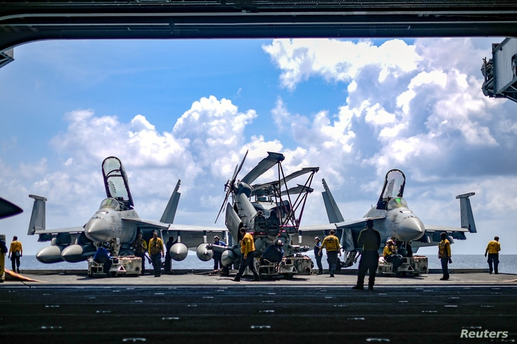 U.S. Navy sailors move aircraft from an elevator into the hangar bay of the aircraft carrier USS Theodore Roosevelt in the…