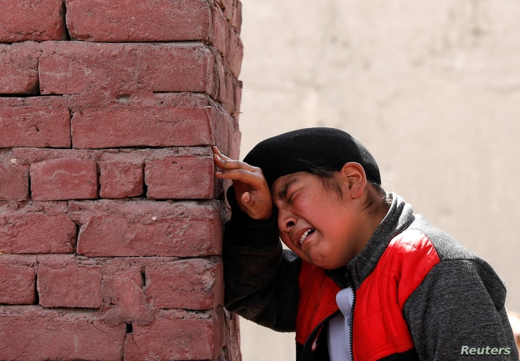 An Afghan Sikh boy mourns the victims who were killed during yesterday's attack at Sikh religious complex during a funeral in…