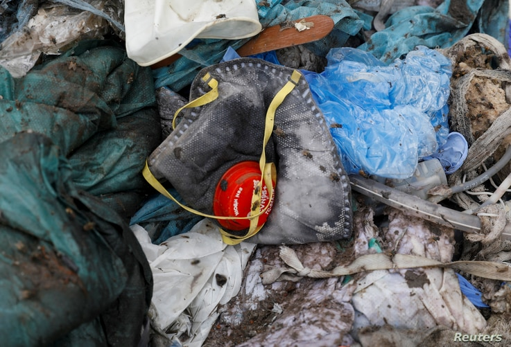 A discarded N95 protective face mask lies amongst other bits of disposed medical waste at a landfill site, during the…
