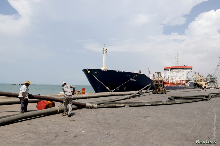 FILE PHOTO: Workers prepare to unload a fuel shipment from an oil tanker at the port of Hodeida, Yemen October 17, 2019…