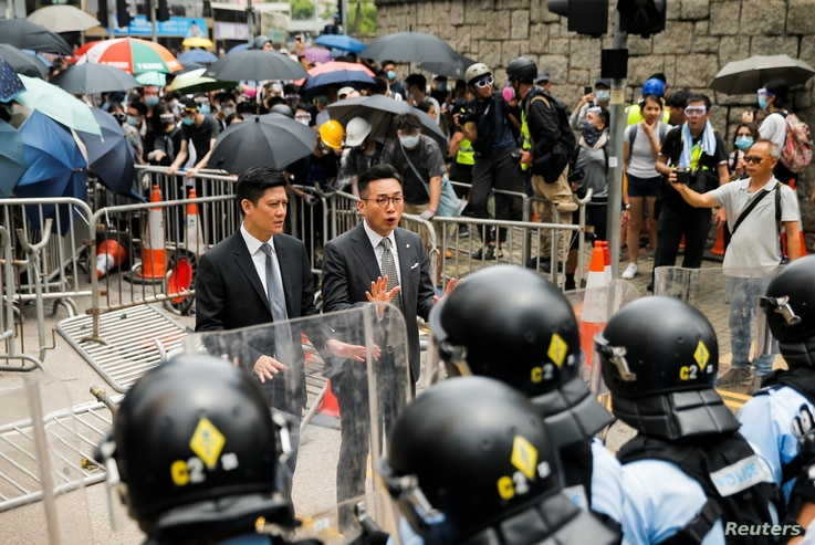 Lawmakers Jeremy Tam and Alvin Yeung of the Hong Kong Civic Party speak in front of a row of riot police officers during a…