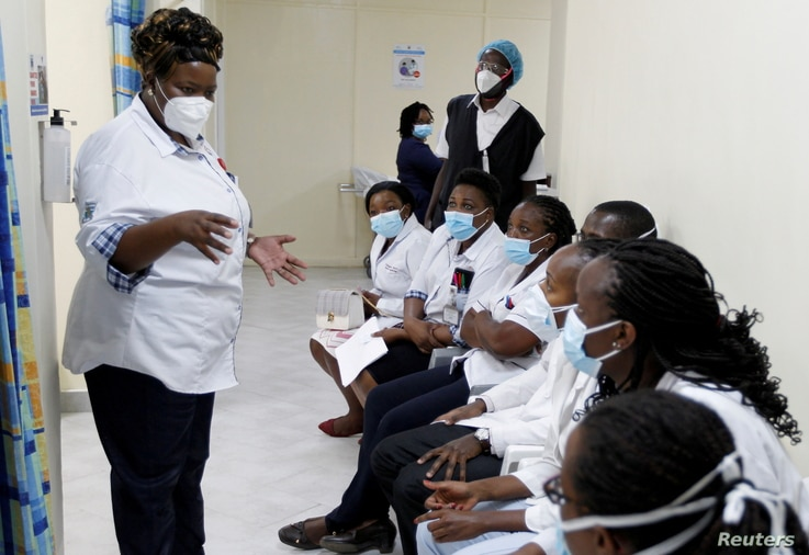 FILE PHOTO: A health worker talks to colleagues as they prepare to receive a coronavirus vaccine at the Kenyatta National…