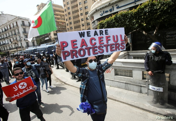 FILE PHOTO: Demonstrators march with banners and flags during a protest demanding political change, in Algiers, Algeria April 9…