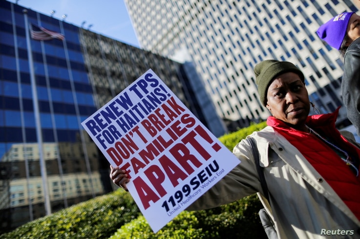 FILE PHOTO: A woman holds a placard as Haitian immigrants and supporters rally to reject DHS Decision to terminate TPS for...