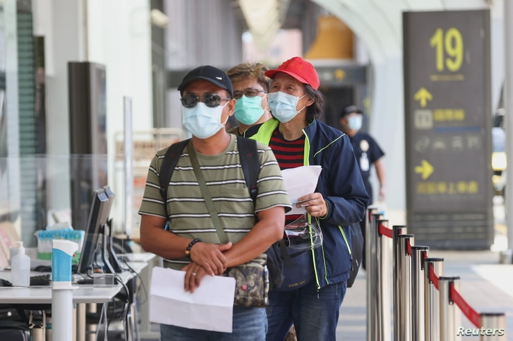 People line up to get their coronavirus disease (COVID-19) test at Songshan airport, Taiwan.