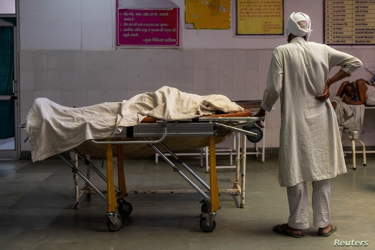 A man stands next to the body of his wife, who died due to breathing difficulties, inside an emergency ward of a government-run…
