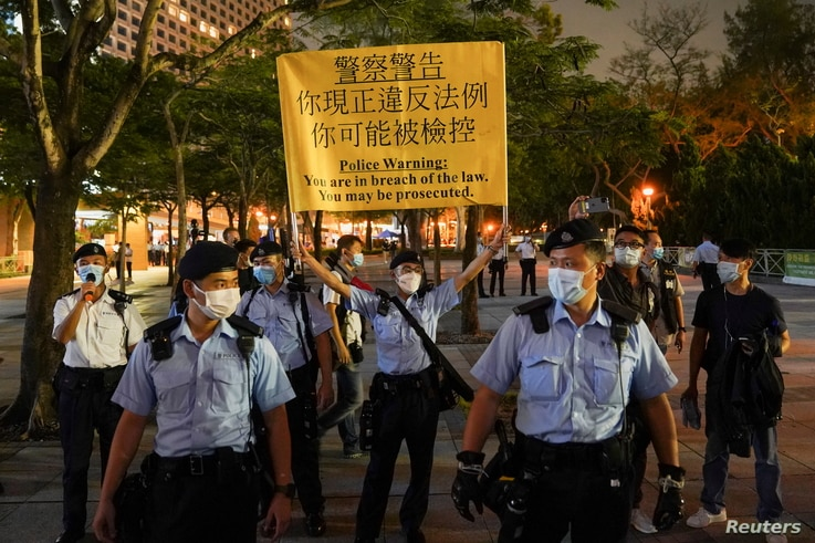 Police officers disperse people mourning at Victoria Park on the 32nd anniversary of the crackdown on pro-democracy…