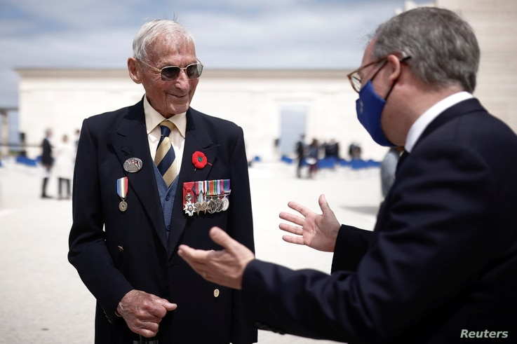 Lord Edward Llewellyn, British Ambassador to France, speaks with veteran David Mylchreest, 97, after the official opening…