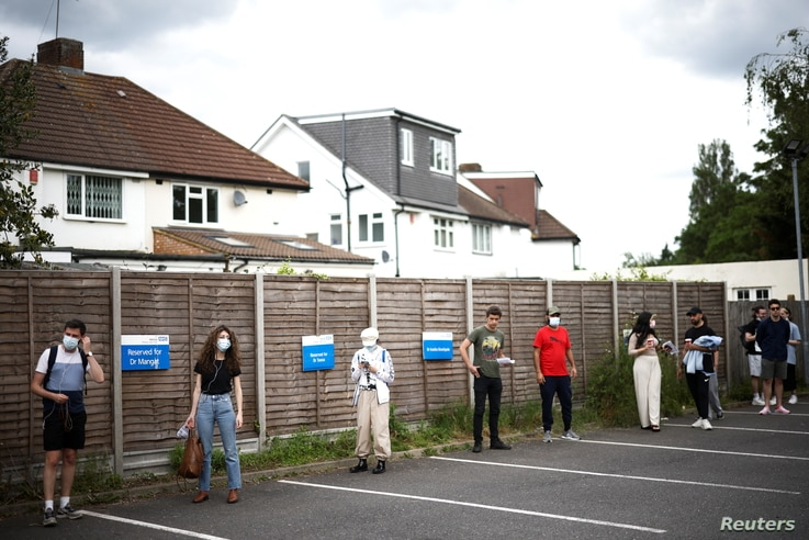 People queue outside a vaccination centre for those aged over 18 years old at the Belmont Health Centre in Harrow, amid the…