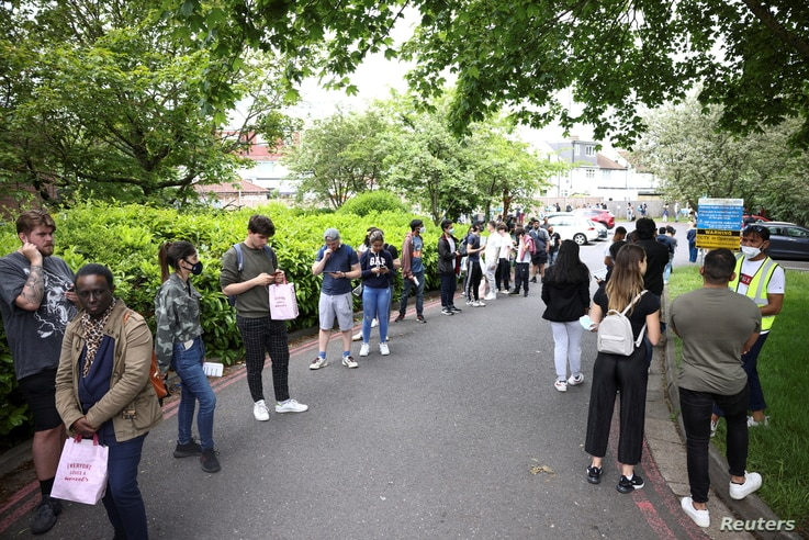 People queue outside a vaccination centre for those aged over 18 years old at the Belmont Health Centre in Harrow, amid the...