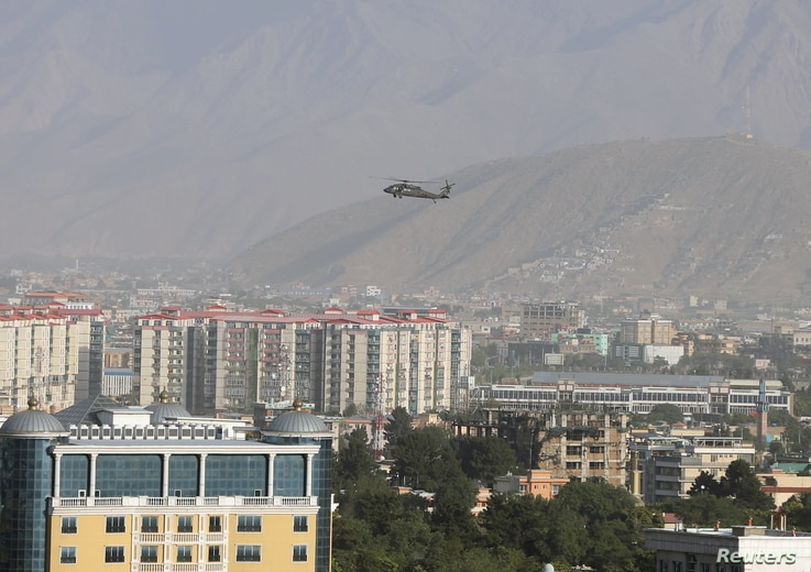 FILE - A NATO helicopter flies over the city of Kabul, Afghanistan.