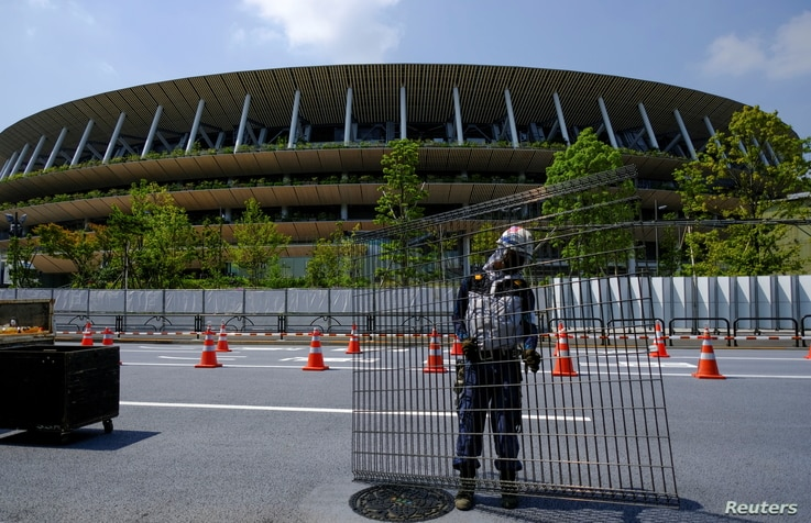 Workers install additional security fence outside Olympic Stadium (National Stadium) for the 2020 Tokyo Olympic Games, that…