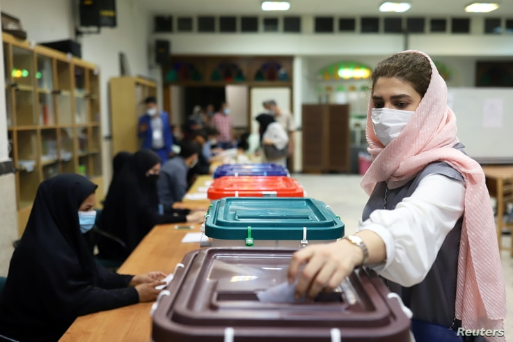 An Iranian woman casts her vote during the presidential election at a polling station in Tehran, Iran June 18, 2021. Majid…