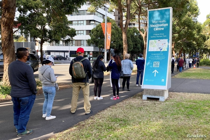People wait in line outside a coronavirus disease (COVID-19) vaccination centre at Sydney Olympic Park in Sydney, Australia,...