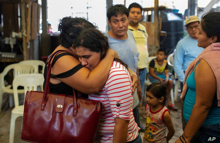 Guadalupe Severo, the wife of slain journalist Julio Valdivia, is embraced during his wake inside their home in Tezonapa,…