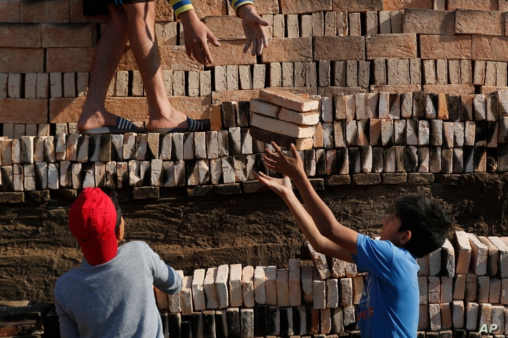 Children work with relatives to load a brick kiln for firing in Tobati, Paraguay, Friday, Sept. 4, 2020. Members of brick…