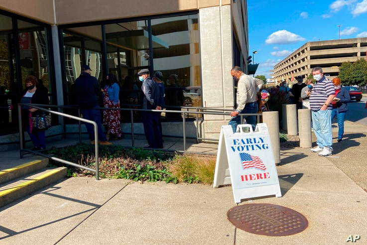 Voters line up outside a polling place Wednesday, Oct. 21, 2020, in Charleston, W.Va. Wednesday marked the first day of early…