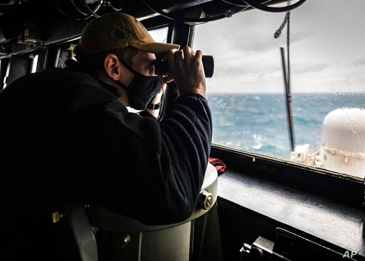 In this photo provided by U.S. Navy, Ensign Grayson Sigler, from Corpus Christi, TX., scans the horizon while standing watch in...