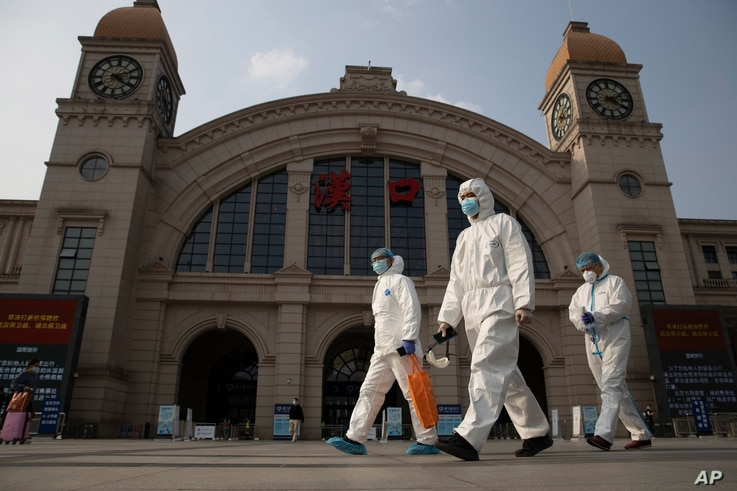 FILE - In this April 7, 2020, file photo, workers in protective suits walk past the Hankou railway station on the eve of its…