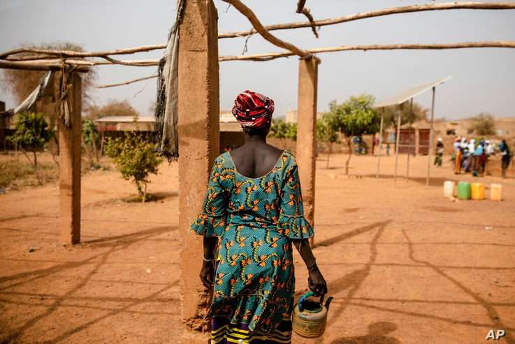 A displaced woman walks with a kettle Monday Feb. 8, 2021 in the Kaya camp, 100 kms North of Ouagadougou, Burkina Faso. A…