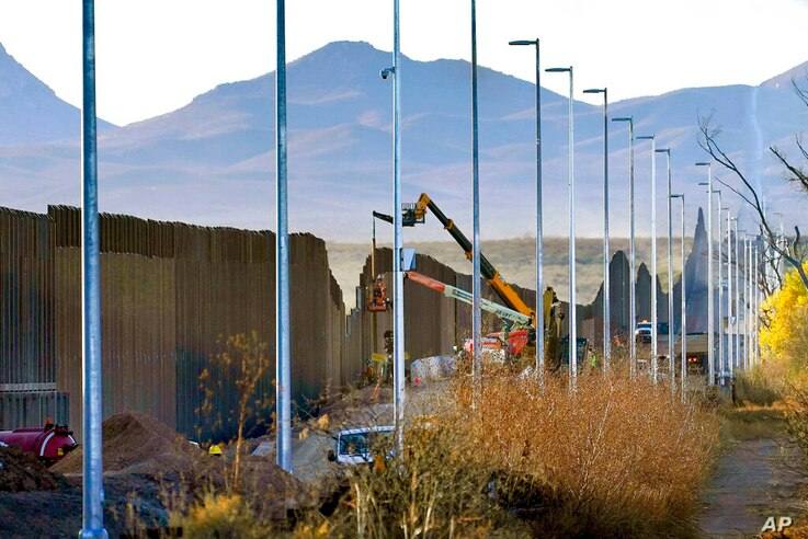 FILE - In this Dec. 8, 2020, file photo, crews construct a section of border wall in San Bernardino National Wildlife Refuge in...