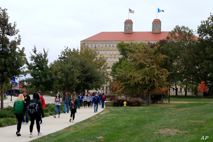 FILE - In this Oct. 24, 2019, file photo students walks in front of Fraser Hall on the University of Kansas campus in Lawrence,…