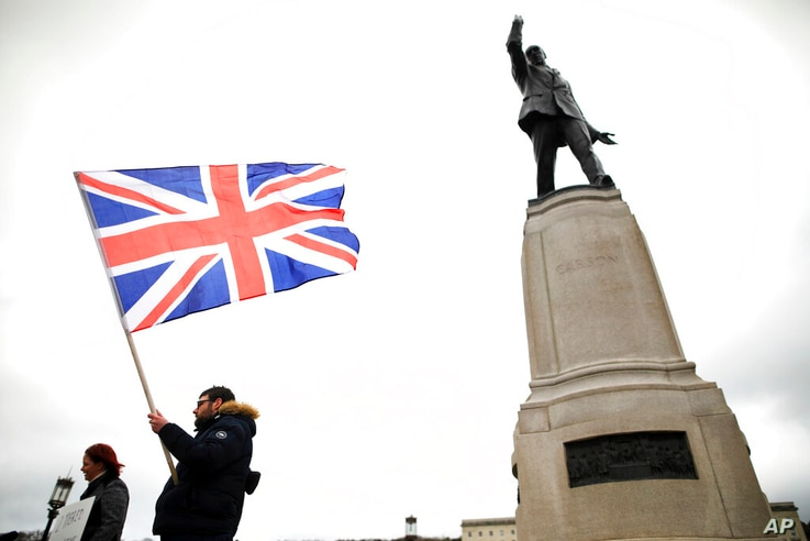 Loyalist protesters opposed to the Northern Ireland Protocol on Brexit make their point under the statue of former Unionist…