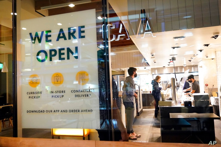 FILE - This Tuesday, March 16, 2021, file photo shows a sign advertising a restaurant opening, in Santa Monica, Calif…
