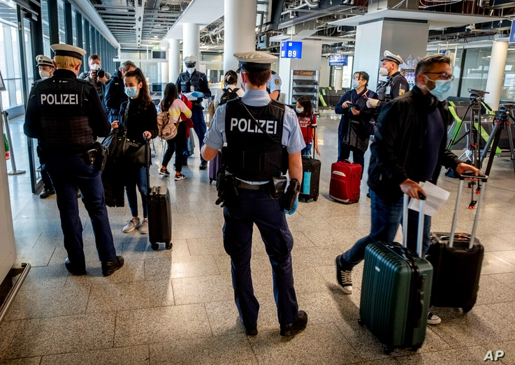 FILE - In this March 30, 2021, file photo, German federal police officers check passengers arriving from Palma de Mallorca for…