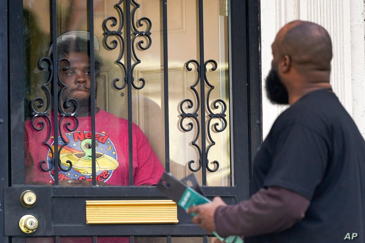 Anthony Brinson, right, talks with a resident while leaving a flyer at a home in Detroit, Tuesday, May 4, 2021. Officials are...