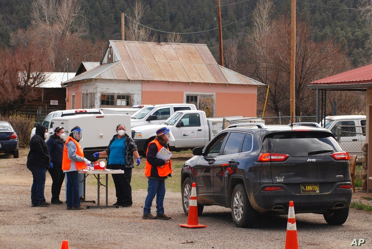 FILE - In this April 20, 2021, file photo medical workers and volunteers administer the coronavirus vaccine at a drive-thru...