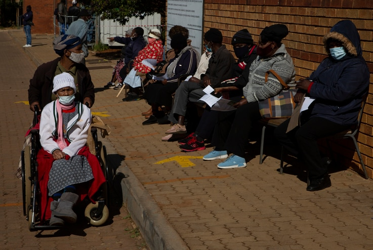 An elderly woman leaves as otherw wait to receive the Pfizer COVID-19 vaccine, at a clinic at Orange Farm, near Johannesburg,…