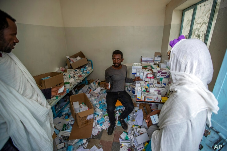 A pharmacist, center, speaks to patients as he sits among the packages of medicine able to be recovered in Hawzen, in the…