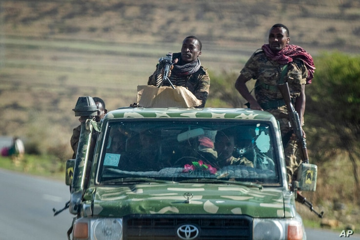Ethiopian government soldiers ride in the back of a truck on a road near Agula, in the Tigray region of northern Ethiopia…