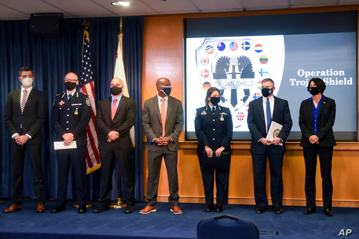 Law enforcement officials stand in front of an Operation Trojan Shield logo at a news conference held to announce Operation...