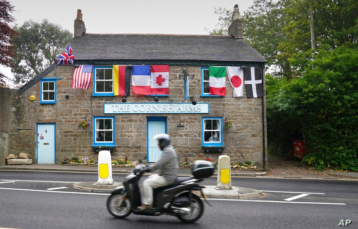 A man rides a motorbike past a pub with flags of the G7 nations and the flag of Cornwall in St. Ives, Cornwall, England,…