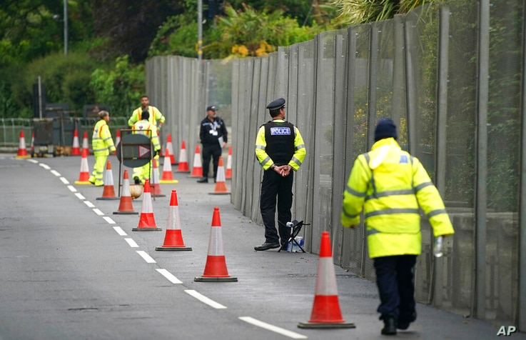Police officers stand guard outside a security gate around Tregenna Castle in Carbis Bay, Cornwall, England, Wednesday, June 9,…