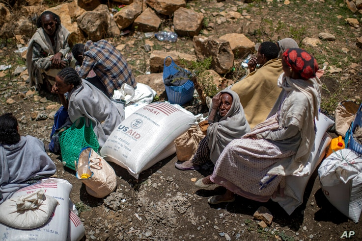An elderly Ethiopian woman sits next to a sack of wheat after it was distributed to her by the Relief Society of Tigray in the...
