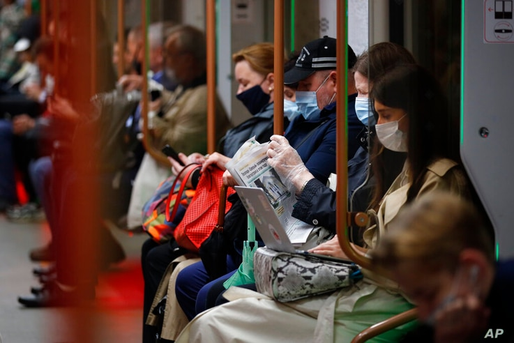 People wearing face mask to help curb the spread of the coronavirus ride a subway car in Moscow, Russia, Thursday, June 10,…