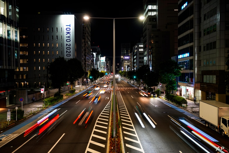 This long exposure photo shows streaks of lights from cars passing by a Tokyo 2020 Olympics and Paralympics sign on the side of...