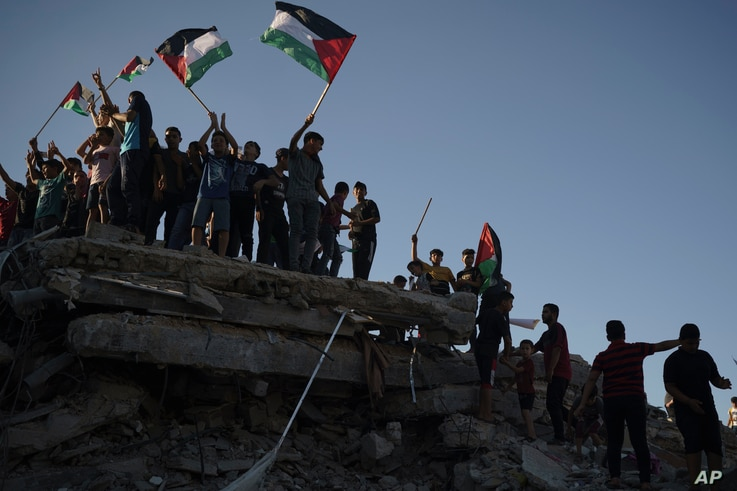 Protesters wave Palestinian flags as they stand atop the rubble of a building destroyed by an Israeli airstrike last month,…