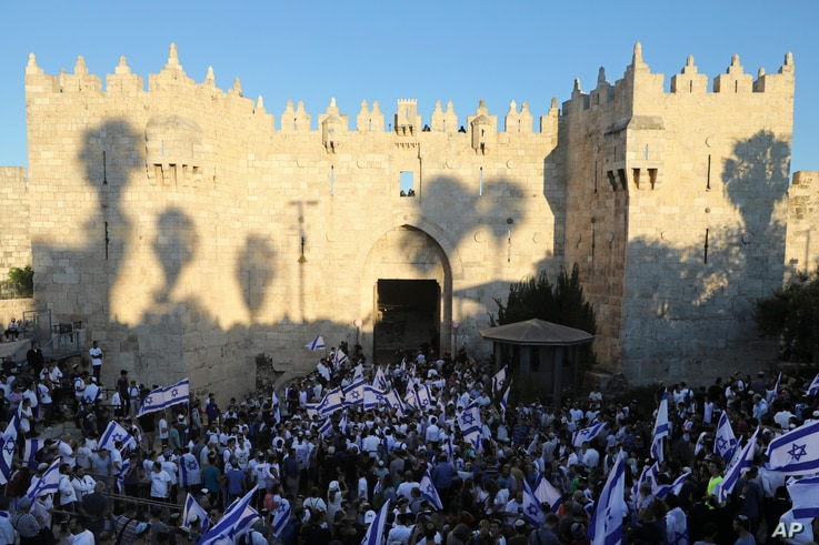 """Jewish ultranationalists wave Israeli flags during the """"Flags March,"""" next to Damascus gate, outside Jerusalem's Old City, June 15, 2021."""