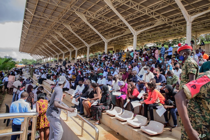 People wait in the stands to receive coronavirus vaccinations at the Kololo airstrip in Kampala, Uganda, Monday, May 31, 2021…